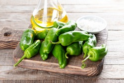 Fresh green pimientos or padron peppers, sea salt, olive oil on a wooden table. Spanish cuisine. Selective focus. Pimientos de Padron.