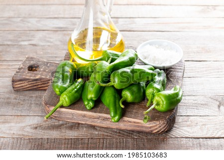 Fresh green pimientos or padron peppers, sea salt, olive oil on a wooden table. Spanish cuisine. Selective focus. Pimientos de Padron. Foto stock ©