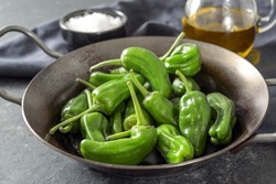 Fresh green pimientos or peppers de padron in an iron pan. Fried in olive oil, and sprinkled with sea salt is a typical tapa meal in Spain. Dark gray background, selected focus, narrow depth of field