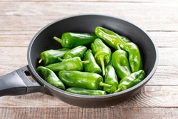 Fresh green pimientos or peppers de padron in frying pan. Fried in olive oil, and sprinkled with sea salt is a typical tapa meal in Spain. selected focus, narrow depth of field