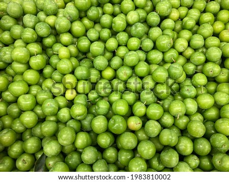 Fresh green plum and pattern on the counter