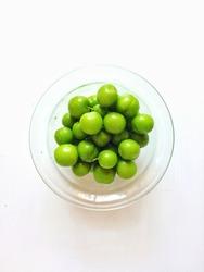 Fresh green plums in a bowl. Fruit eaten in the season.