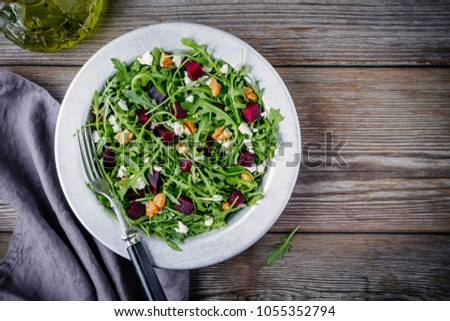 Fresh green salad with arugula, beets, walnuts and feta cheese on wooden background