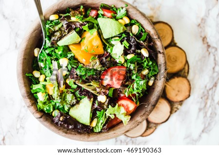 fresh green salad with avocado and corn in wooden plate on a light background,healthy lifestyle and raw food concept,top view #469190363