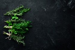 Fresh green spices and herbs. Dill, parsley, rosemary. On a black stone background. Top view. Free copy space.