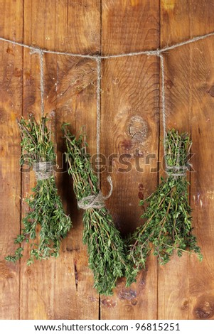 fresh green thyme hanging on rope on wooden background - stock photo