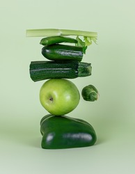 Fresh green vegetables and fruits on a green background. Equilibrium floating food balance.