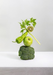 Fresh green vegetables and fruits on table. Equilibrium floating food balance