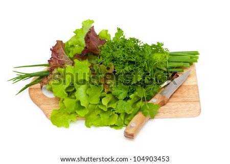 fresh green vegetables and herbs on cutting board isolated on white