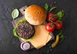 Fresh grilled and raw minced pepper beef burger on vintage chopping board with buns onion and tomatoes on black background. Salty pickles and basil. Top view