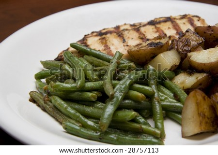 Fresh grilled chicken and potatoes with green beans on a white dinner plate.