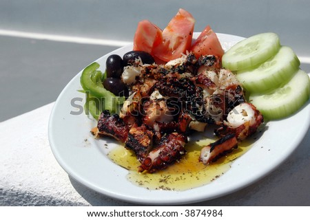 fresh grilled octopus salad greek with olives tomatoes peppers and cucumber on stone wall photographed in the Greek Islands