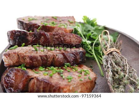 fresh grilled red meat with thyme on metal pan isolated on white background