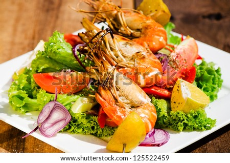 Fresh grilled shrimps on a plate with vegetable and a wood table as background