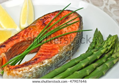 Fresh grilled sockeye salmon steak dinner with asparagus and lemon wedges