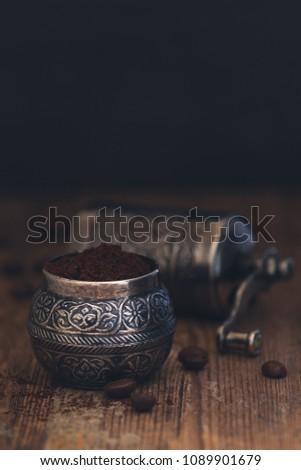 Fresh ground coffee in a vintage metal manual manual coffee grinder on a rustic wood background