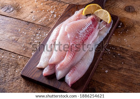 Fresh haddock fillets on a rustic table top with lemon wedges. ストックフォト ©