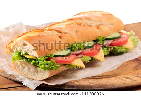 Fresh ham and cheese salad submarine sandwich on old wooden cutting board with isolated white background