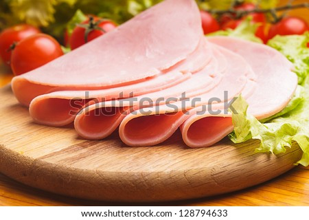 Fresh ham slices with lattuce and cherry tomato on the wooden board