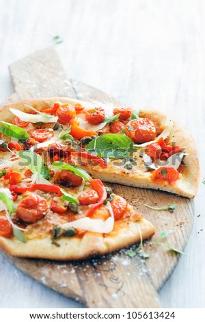 Fresh, handmade pizza with oven roasted tomatoes, peppers, capers, basil and shaved cheese on rustic wooden board