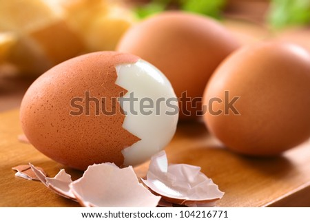 Fresh hard boiled eggs with shell beside on wooden board (Selective Focus, Focus on the front of the shell on the first egg)