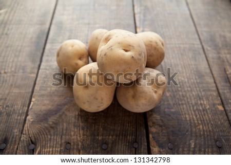 Fresh harvested potatoes on a rough wooden surface.