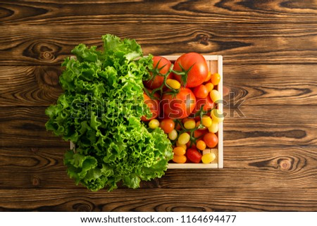 Fresh head of leafy green lettuce and a variety of ripe juicy tomatoes in a small wooden crate at wooden table at an organic farmers market on a wooden table viewed top down #1164694477
