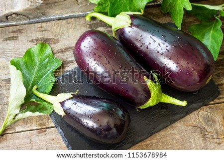 Fresh healthy raw Purple Eggplant on a kitchen wooden table. The concept of Diet menu.  Сток-фото ©