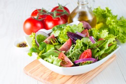 Fresh healthy vegetable salad made of cherry tomato, ruccola, arugula, feta, olives, cucumbers, onion and spices. Greek Caesar salad in a  bowl on wooden background. Healthy organic diet food concept