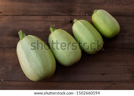 Fresh healthy zucchini courgette on brown wooden background #1502660594