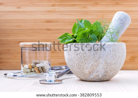 Fresh herbal leaves basil ,sage , mint ,holy basil ,fennel and capsule of herbal medicine alternative health care with stethoscope setup on wooden background.