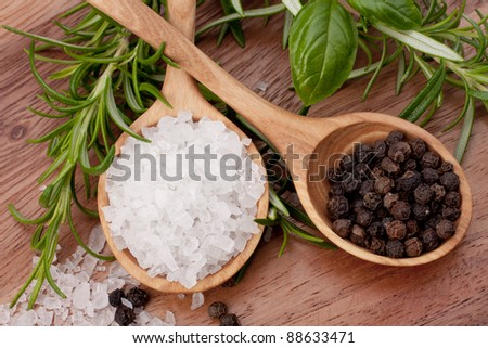 Fresh herbs and salt spoon on vintage wooden background. Shallow focus.