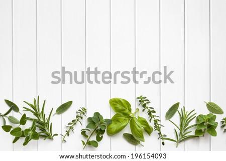 Fresh herbs border over white timber panel background.