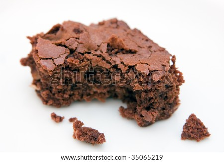 Fresh home-made chocolate brownie with bite-shaped chunk missing, on a white background - stock photo