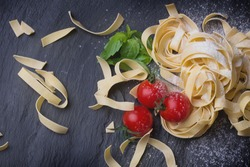 Fresh home made Italian pasta with  basil leaves, flour, asparagus and tomatoes on the slate board