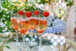 Fresh home made summer cocktail with champagne, peppermint and fresh strawberries