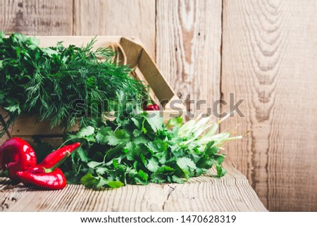 Fresh homegrown aromatic culinary herbs, hot red peppers in wooden crate on rustic table, plant based food, local produce. Organic green leaf vegetables, parsley, dill, cilantro, healthy  vegan eating