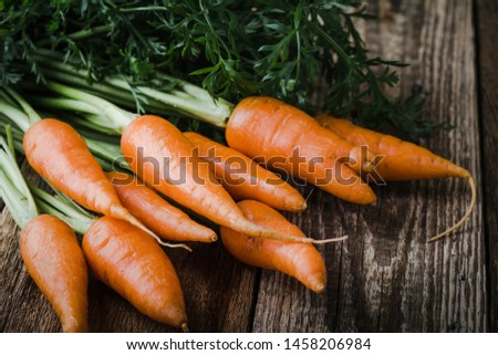 Fresh homegrown carrots on wooden rustic table, plant based food, local food, close up