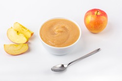 Fresh homemade applesauce. The concept of proper nutrition and healthy eating. Organic and vegetarian food. White bowl with fruit puree on fabric and cut apples on table. Baby food. Close up
