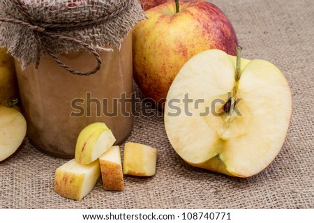 Fresh homemade applesauce with raw apples on a textile background