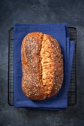 Fresh homemade artisan bread with seeds on dark gray surface. Top view. Copy space. Bread bakery background concept. Close up.