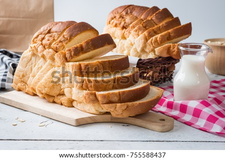 Fresh homemade  baked bread and sliced bread with milk on rustic white wooden table