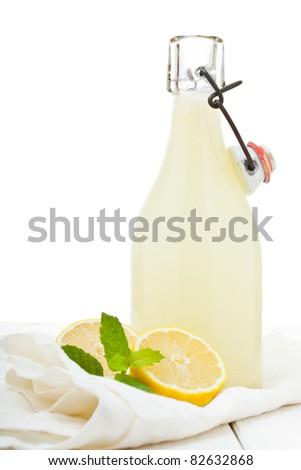 Fresh homemade bottle of lemonade on wooden table