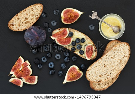 Fresh homemade bread, homemade baking. Blank for sandwich, figs, blueberries, sauce. Top view. Black stone background.