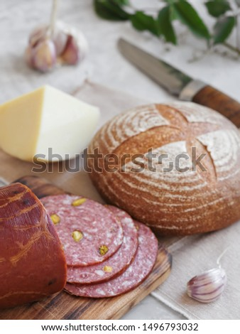 Fresh homemade bread, homemade baking. Preparation for a sandwich, salami with pistachios, cheese, onions, garlic, sauce. close-up.