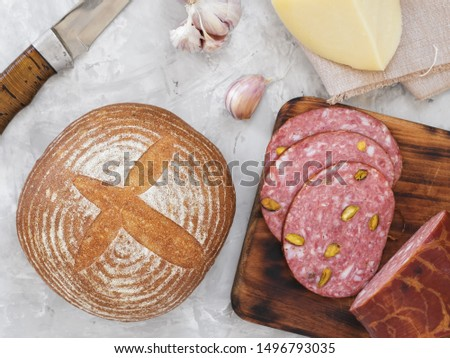 Fresh homemade bread, homemade baking. Preparation for a sandwich, salami with pistachios, cheese, onions, garlic, sauce. Top view