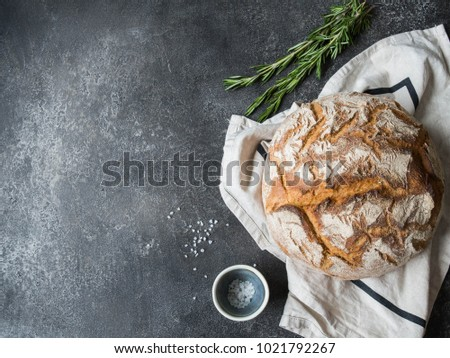 Fresh homemade bread on a linen towel, rosemary and sea salt  on a gray background. Top view. Copy space