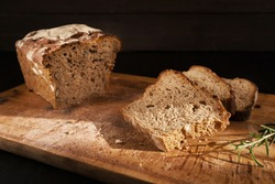 Fresh homemade bread, partially sliced. Bread is located on a wooden surface. Hobbies, baking rye bread at sourdough at home. Healthy food concept, traditional craft bread. Closeup