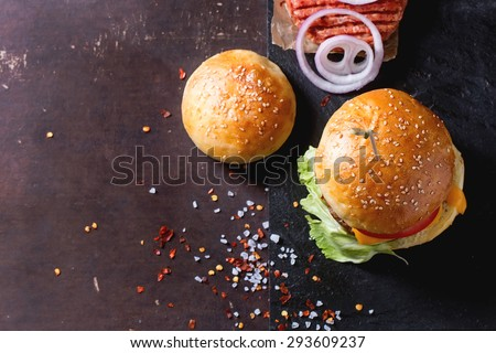 Fresh homemade burger on black slate and raw cutlet and sliced onion, served with sea salt and pepper over dark background. Top view. With copy-space on left.