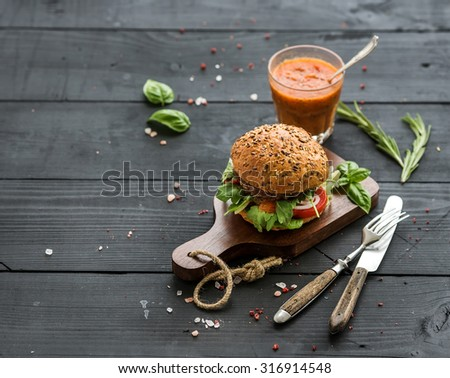 Fresh homemade burger on dark serving board with spicy tomato sauce, sea salt and herbs over dark wooden background, copy space